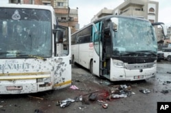 A photo released by the Syrian official news agency SANA shows blood-soaked streets and several damaged buses in a parking lot at the site of twin explosions in Damascus, Syria, March 11, 2017.