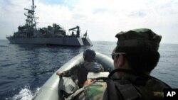 Des ingénieurs à bord d'un canot gonflable s'approchent du patrouilleur américain, l'USS Thunderbolt, dans la mer Adriatique, 13 juin 2000.