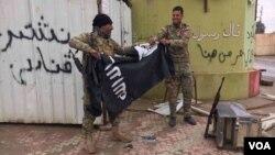 Dua tentara Irak merobek bendera ISIS di Mosul, Irak (foto: ilustrasi). Kelompok ekstremis ISIS terus kehilangan wilayah kekuasaannya di Irak dan Suriah.