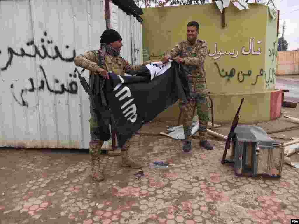 Two Iraqi forces tear IS flag. (Kawa Omar/VOA Kurdish)