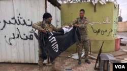 Two Iraqi troops tear an ISIS flag apart. (Kawa Omar/VOA Kurdish)