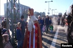 FILE - Children in Munich, Germany, get a surprise visit from St. Nicholas before they board an old-fashioned steam train for a special Christmas ride with him.