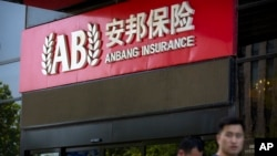 People walk past an entrance to the Anbang Insurance Group's offices in Beijing, June 14, 2017.