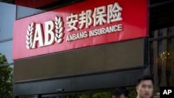 图片说明:路人经过位于北京市的安邦保险公司门前。(2017年6月14日照片)