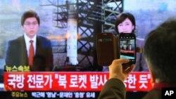 12일 한국 서울역에서 북한의 장거리 로켓 발사 소식을 지켜보는 주민.