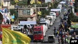 Bendera Hezbollah berkibar menyambut kedatangan tanker yang membawa minyak Iran di al-Ain, Hermel, di Lembah Bekaa, Lebanon timur 16 September 2021. (AFP)