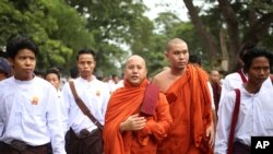 ຄູບາຫົວຊາດນິຍົມ Wirathu (ກາງ) ເດີນຂະບວນສະໜັບສະໜູນ ການອອກມາດຕະການໃໝ່ ຈຳກັດການແຕ່ງງານກັບ ສາສະໜາອື່ນໆ ຢູ່ໃນນະຄອນ Mandalay.
