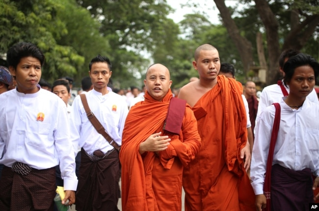 FILE - Nationalist Buddhist monk Wirathu, center, marches to celebrate newly imposed restrictions on interfaith marriages in Mandalay, the second largest city in Myanmar, Sept. 21, 2015.