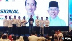 Jokowi menghadiri Rakernas Tim Kampange Nasional Indonesia Kerja di Surabaya, Minggu 28/10. (foto Petrus Riski/VOA)