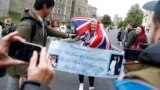 A Royal fan carrying a banner is interviewed by a member of the media, outside Windsor Castle in Windsor, south England, Monday May 6, 2019, after Prince Harry announced that his wife Meghan, Duchess of Sussex, has given birth to a boy. (AP Photo/Alastair Grant)