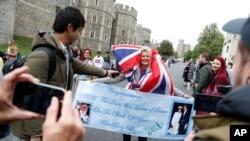 Un fanático de la realeza Royal lleva una pancarta en las afueras del Castillo de Windsor en Windsor, sur de Inglaterra, el lunes 6 de mayo de 2019, después de que el príncipe Harry anunció que su esposa Meghan, duquesa de Sussex, había dado a luz a un niño.
