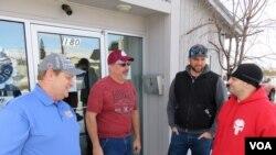 凯里·伍达德(左)和克里斯·莫雷尔斯(右)等几位美国铝业公司(Alcoa)的工人在华盛顿州东韦纳奇的工会会所叙旧。