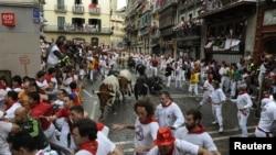 "Para pelari mencoba untuk menghindari banteng petarung ""Dolores Aguirre"" di sudut Estafeta di putaran pertama Festival San Fermin di Pamplona (7/7). Menurut media lokal, satu orang terkena tanduk dan empat lainnya terluka dalam kegiatan lari tahunan yang"