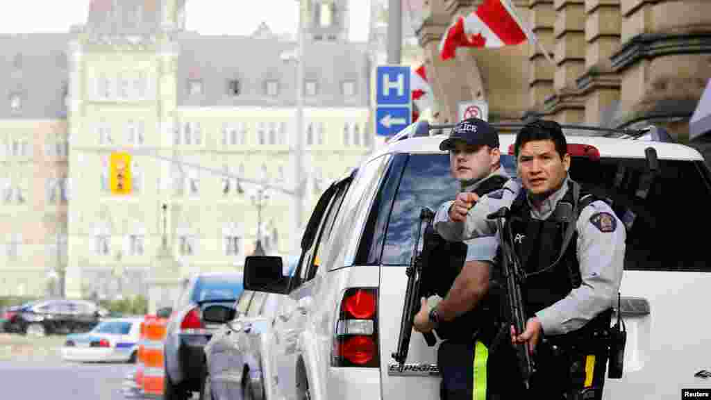 Armed Royal Canadian Mounted Police officers guard access to Parliament Hill following a shooting incident in Ottawa, Canada, Oct. 22, 2014.