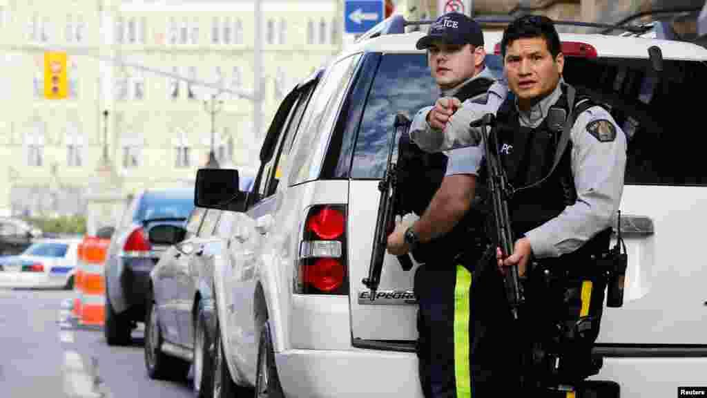 Des agents de la Gendarmerie royale du Canada. armes à la main, gardent l'accès à l'entrée du Parlement après une fusillade à Ottawa, le 22 octobre 2014. REUTERS/Chris Wattie