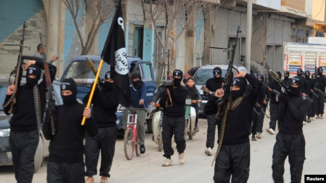 Fighters of al-Qaida linked Islamic State of Iraq and the Levant carry their weapons during a parade at the Syrian town of Tel Abyad, near the border with Turkey, Jan. 2, 2014.
