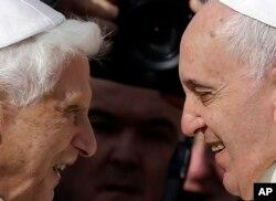 El papa emérito Benedicto XVI, izquierda, y el papa Francisco se saludan durante un encuentro en 2014.