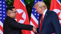 Ông Kim Jong Un bắt tay ông Trump trong cuộc gặp thượng đỉnh ở Singapore giữa năm ngoái.