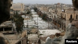 FILE - A general view shows damaged buildings along a deserted street and an area controlled by forces loyal to Syria's President Bashar Al-Assad, as seen from a rebel-controlled area at the Bab al-Nasr frontline in Aleppo, Feb. 10, 2015.