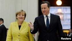 Britain's Prime Minister David Cameron accompanies German Chancellor Angela Merkel as they visit the British Museum in London, Jan. 7, 2015.