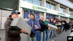 Volunteers of the Azov Civil Corps pass stones to each other to build a wall in front of the central branch of Russian Sberbank during a protest in Kyiv, Ukraine, March, 13, 2017.