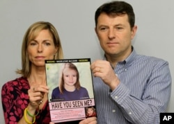 FILE - Kate and Gerry McCann pose with a missing poster, an age progression computer generated image of their daughter Madeleine at 9 years old, as they mark their daughter Madeleine's birthday and the fifth anniversary of her disappearance in London, May 2, 2012.