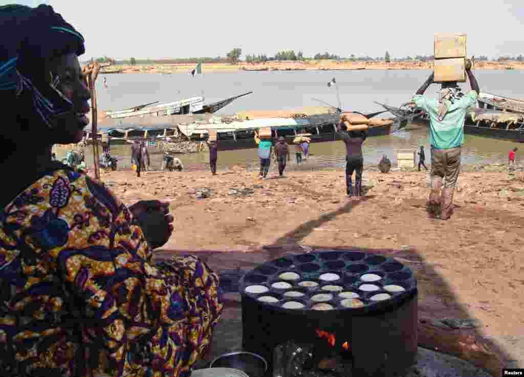 Une Malienne observant des manoeuvres qui transportent des vivres à Mopti.