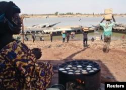 FILE - A Malian woman looks at men carrying humanitarian food aid, Mopti, Mali, Feb. 4, 2013.