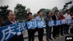 """Những người ủng hộ ông Lưu Hiểu Ba đứng bên ngoài một công viên ở Bắc Kinh, cầm những tấm bảng ghi rằng """"Chúng tôi mừng ông Lưu Hiểu Ba đoạt giải Nobel Hòa bình"""""""
