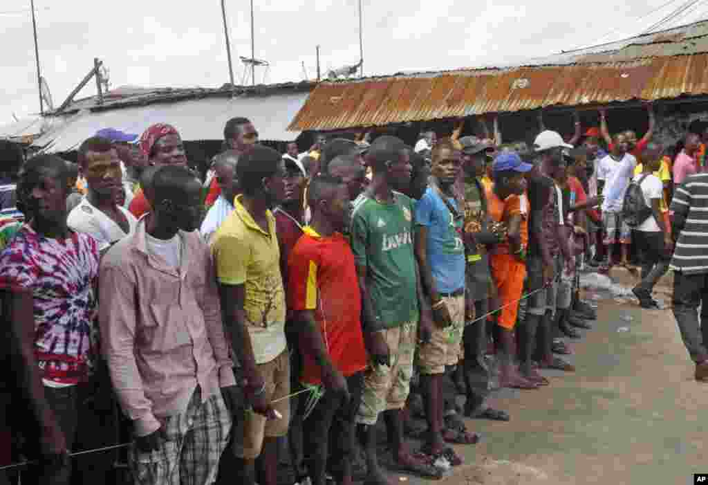 West Point residents stand behind a green string marking a holding area, as they wait for a second consignment of food from the Liberian Government, at the West Point area, Monrovia, Liberia, Aug. 22, 2014.