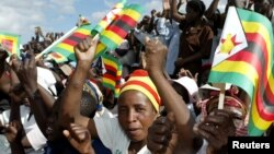 FILE: Zimbabwe political supporters wave flags in Gutu, a rural town 220 Km's south-east of the capital [Harare].