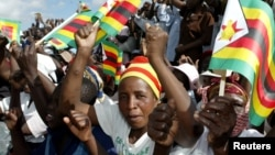 FILE - Zimbabwe political supporters wave flags in Gutu, a rural town 220 Km's southeast of the capital Harare.