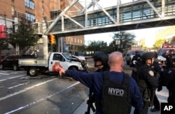 In this photo provided by the New York City Police Department, officers respond to a report of gunfire along West Street near the pedestrian bridge at Stuyvesant High School in lower Manhattan in New York, Oct. 31, 2017.