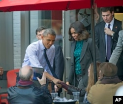 President Barack Obama, accompanied by first lady Michelle Obama, greets patrons after they had lunch with members of the Standing Rock Sioux Tribal Youth at We the Pizza/Good Stuff Eatery restaurant in the Capitol Hill neighborhood of Washington, DC, Nov. 20, 2014.