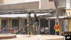 Tentara berjaga-jaga di lokasi ledakan bom di sebuah pasar di Maiduguri, Nigeria (7/3). (AP/Jossy Ola)