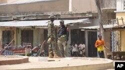 Lực lượng an ninh đứng gác tại hiện trường của vụ nổ bom tại một khu chợ ở Maiduguri, Nigeria, ngày 07 tháng ba 2015.
