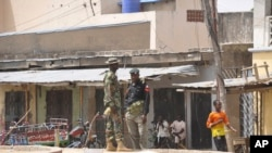 Security forces stand guard at the site of bomb explosion at a market in Maiduguri, Nigeria, March 7, 2015 .