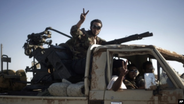 Libyan rebels drive a vehicle mounted with an anti-aircraft gun toward Bin Jawad, August 26, 2011