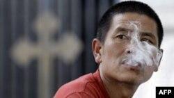 Người đàn ông Trung Quốc hút thuốc bên ngoài một nhà thờ ở Bắc Kinh