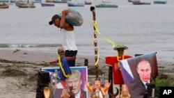 Dos líderes mundiales que preocupan al mundo. Un pescador pasa por delante de un altar con una imagen del presidente electo Donald Trump y del presidente ruso Vladimir Putin, creado por un grupo de chamanes para su ceremonia de Año Nuevo, en la playa Agua Dulce en Lima, Perú.