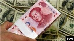 Mata uang Tiongkok, yuan, di antara lembaran dolar Amerika (Foto: dok).