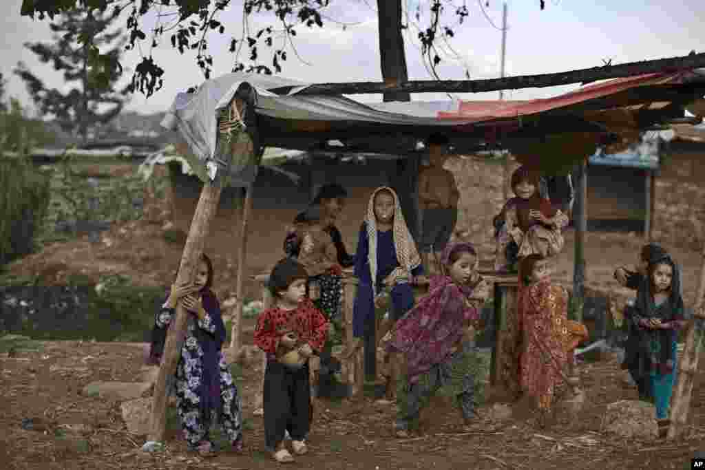 Trẻ em tị nạn Afghanistan tụ tập dưới mái chòi của một người bán thức ăn để trú mưa, ở ngoại ô Islamabad, Pakistan.