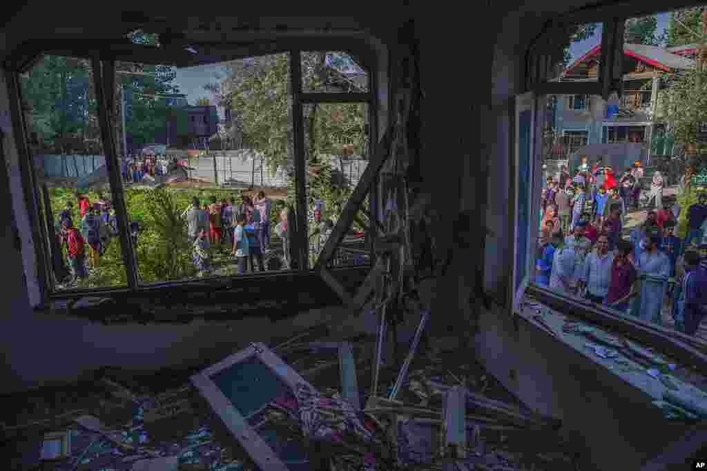 Kashmiris gather outside a house damaged in a gunbattle in the outskirts of Srinagar, Indian controlled Kashmir.