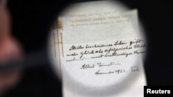 A note written on a Tokyo hotel official paper in 1922 by Albert Einstein is seen before it is sold at an auction in Jerusalem, October 24, 2017. (REUTERS/Ammar Awad)