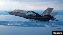 ໂຕຢ່າງເຮືອບິນລົບ F-35 ຂອງທະຫານມາຣິນ ສະຫະລັດ ກຳລັງບິນຂ້າມແມ່ນໍ້າ Patuxent ທີ່ຖານທັບອາກາດ ໃນລັດແມຣີແລນ ວັນທີ 22 ກຸມພາ 2012.