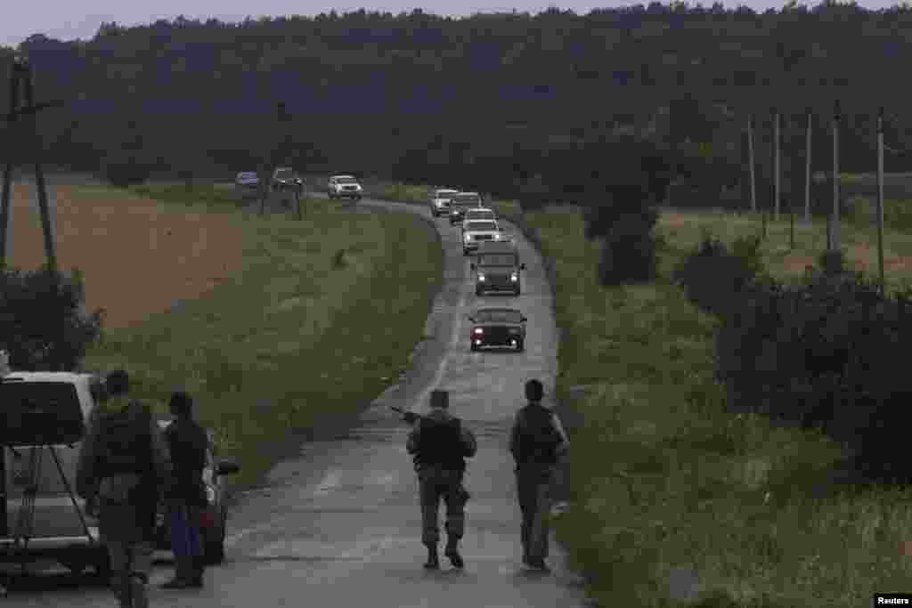 Pro-Russian separatists watch as Organization for Security and Cooperation in Europe (OSCE) monitors arrive at the crash site of Malaysia Airlines flight MH17, near the settlement of Grabovo in the Donetsk region, July 18, 2014.