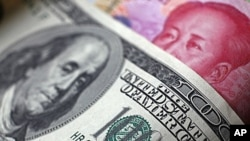 A Chinese 100 yuan banknote is placed under a $100 banknote (top) in this photo illustration.