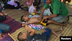 Methas Charojam (tengah), seorang petinju anak berusia 7 tahun, bersiap berlaga di Provinsi Buriram, Thailand, 2 Februari 2018.