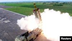 북한이 지난8월 새로 개발한 초대형 방사포를 시험발사했다며 공개한 사진.
