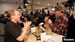Canopy Growth CEO Bruce Linton applauds after handing Ian Power and Nikki Rose, who were first in line to purchase the first legal recreational marijuana at a Tweed retail store in St John's, Newfoundland and Labrador, Canada October 17, 2018. (REUTERS/Chris Wattie)
